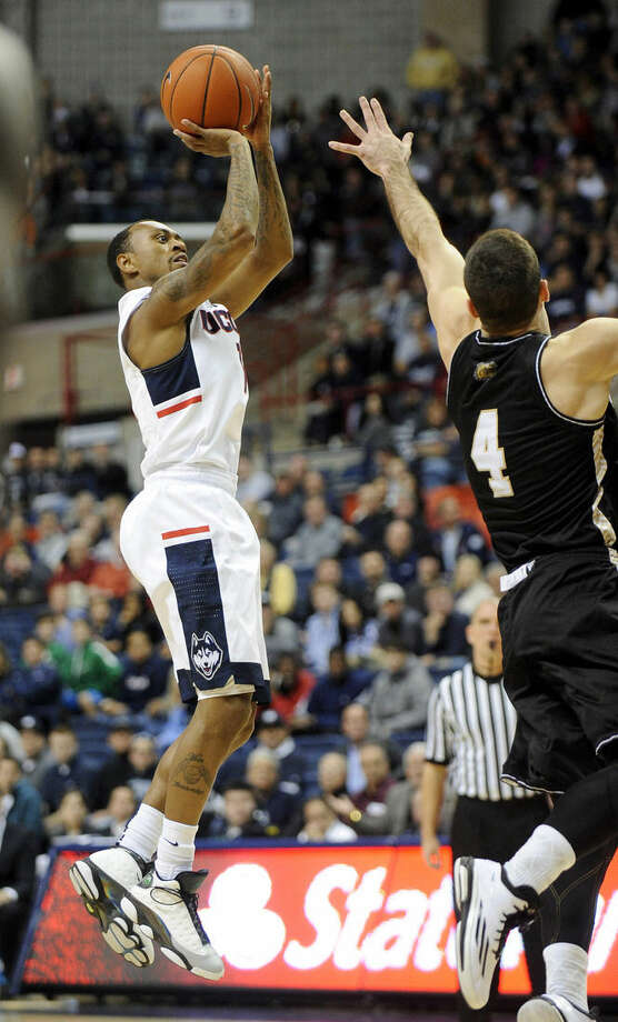 Connecticut's Ryan Boatright, left, shoots over Bryant's Shane McLaughlin (4) during the first half of an NCAA college basketball game in Storrs, Conn., on Friday, Nov. 14, 2014. (AP Photo/Fred Beckham)