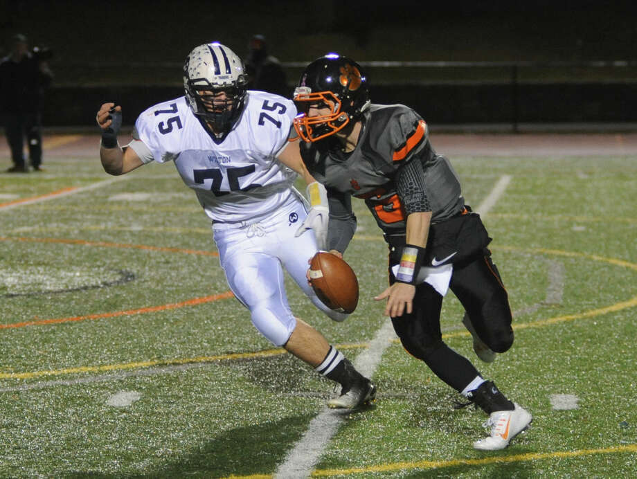 Wilton's Tyler Mirabile (75) chases Ryan Dunn of Ridgefield out of the pocket during Friday's game at Tiger Hollow Stadium.