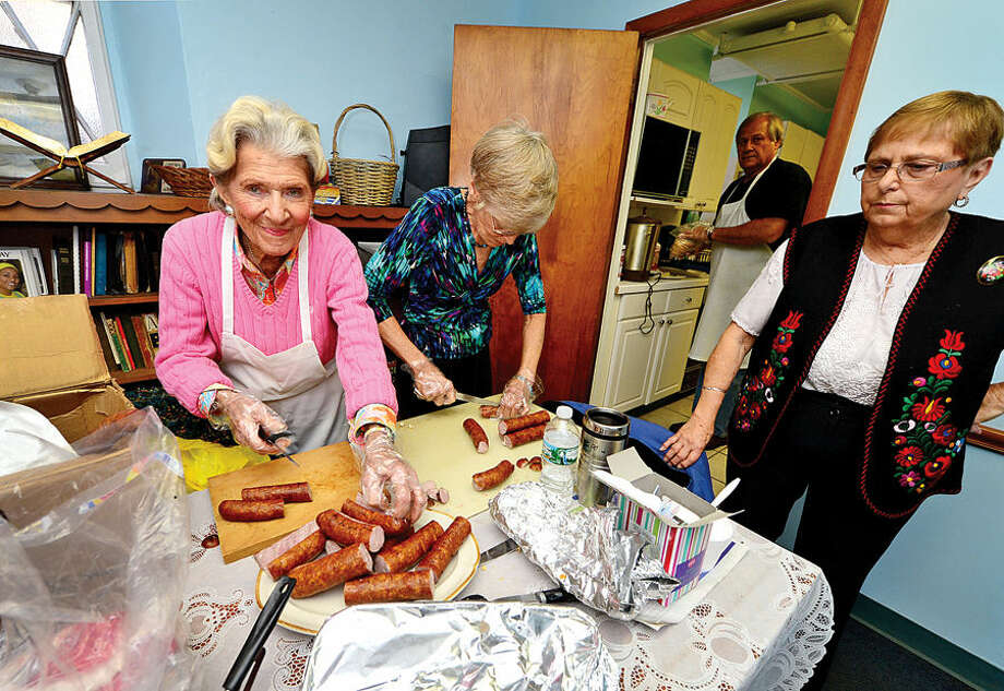 Hour photo / Erik Trautmann Marir Smilansky, Glori Lynn Klein and Brabara Boczer of The Calvin Reformed Church in Norwalk, formerly known as the Hungarian Reformed Church, prepare Kolbasz for it's annual Fall Harvest Hungarian Sausage Sale Saturday.