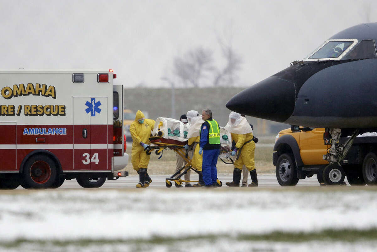 Health workers in protective suits transport Dr. Martin Salia, a surgeon working in Sierra Leone who had been diagnosed with Ebola, from a jet that brought him from Sierra Leone to a waiting ambulance that will take him to the Nebraska Medical Center in Omaha, Neb., Saturday, Nov. 15, 2014. Dr. Salia is the third Ebola patient at the Omaha hospital and the 10th person with Ebola to be treated in the U.S. (AP Photo/Nati Harnik)