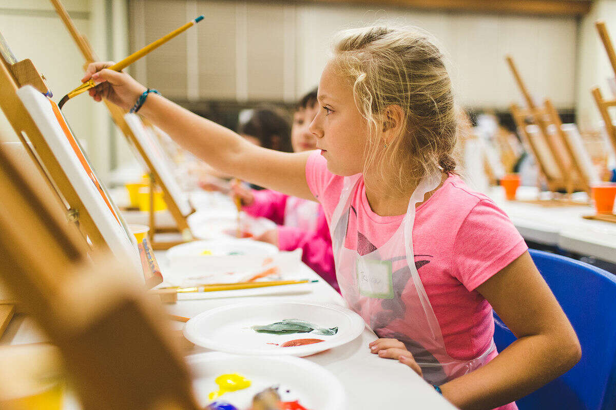 Jessica Schweizer, 11, a sixth grader at West Rocks Middle School carefully paints a picture at the Kids and Canvas Paint Party sponsored by The Hour Newspaper at the Norwalk Public Library Friday evening. DAVID ESPOSITO / Hour Photo