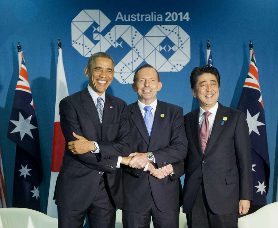 U.S. President Barack Obama, left, Australian Prime Minister Tony Abbott, center, and Japanese Prime Minister Shinzo Abe, right, shake hands at the start of their meeting at the G20 Summit in Brisbane, Australia, Sunday, Nov. 16, 2014. (AP Photo/Pablo Martinez Monsivais)