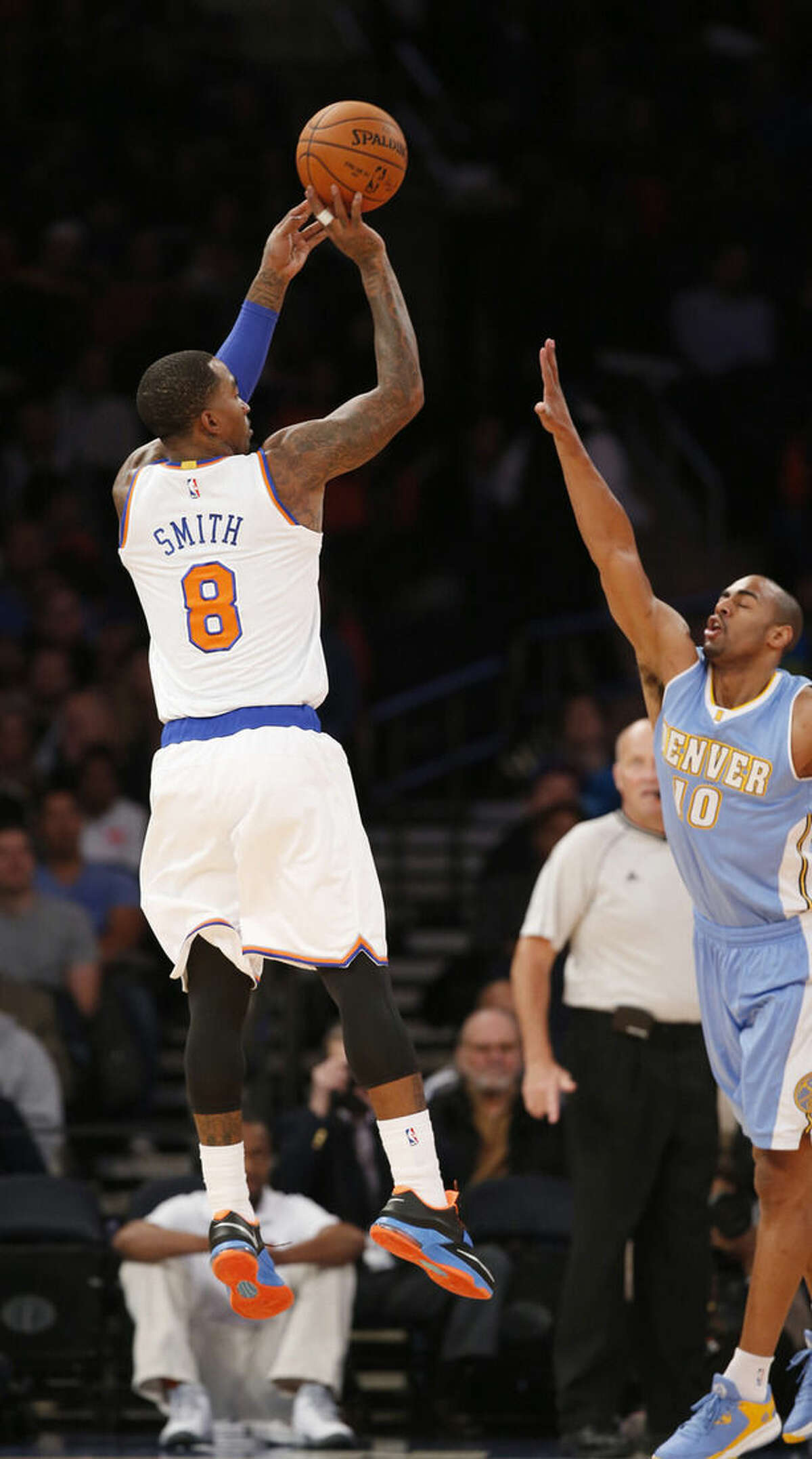 New York Knicks guard J.R. Smith (8) shoots over the defense of Denver Nuggets guard Arron Afflalo (10) in the first half of an NBA basketball game in New York, Sunday, Nov. 16, 2014. (AP Photo/Kathy Willens)