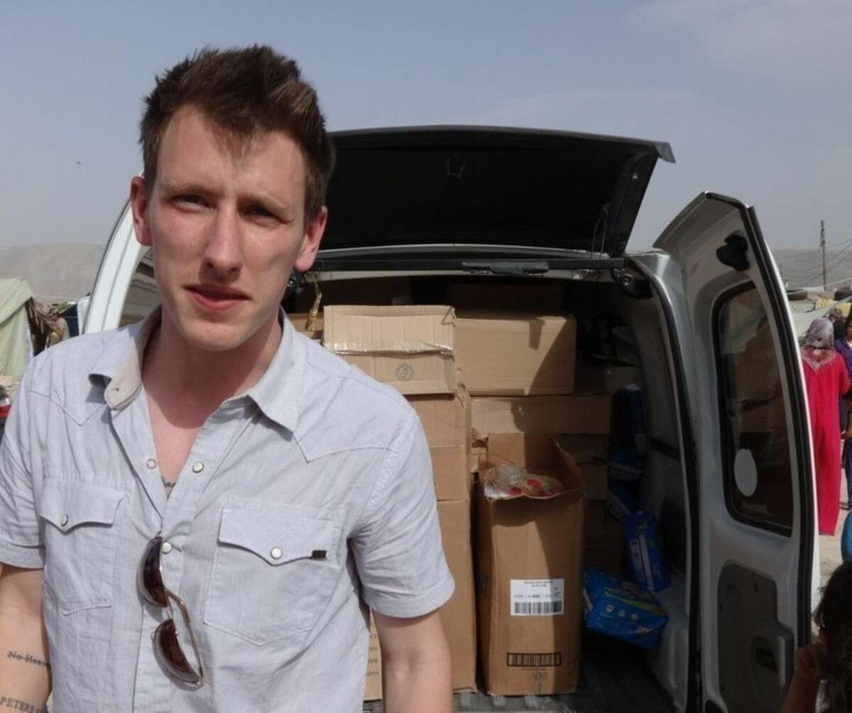 FILE - This undated file photo provided by the Kassig Family shows Peter Kassig standing in front of a truck filled with supplies for Syrian refugees. A new graphic video purportedly produced by Islamic State militants in Syria released Sunday Nov. 16, 2014 claims U.S. aid worker Kassig was beheaded. (AP Photo/Courtesy Kassig Family, File)