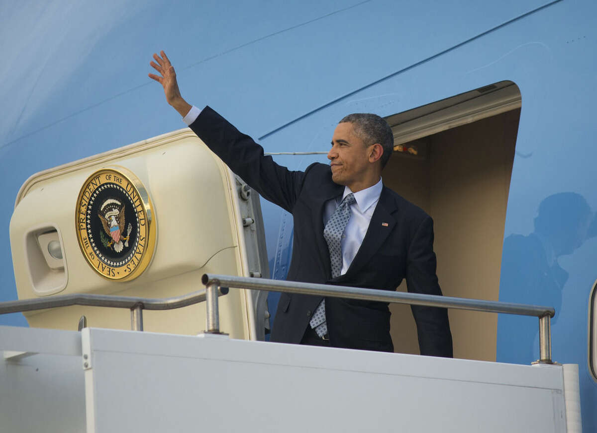 U.S. President Barack Obama waves as he boards Air Force One during his departure at Royal Australian Air Force Base Amberley, Sunday, Nov. 16, 2014 in Australia. Obama is heading back to Washington after visiting China, Myanmar and attending G20 Summit in Australia. (AP Photo/Pablo Martinez Monsivais)