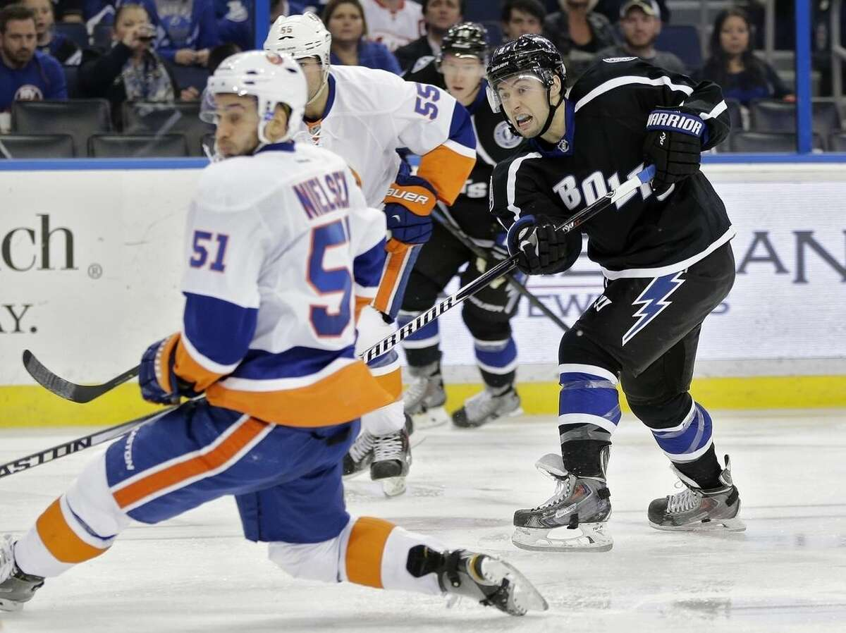Tampa Bay Lightning center Tyler Johnson (9, right) watches his wrist shot get by New York Islanders center Frans Nielsen (51), of Denmark, and goalie Chad Johnson for a goal during the second period of an NHL hockey game Saturday, Nov. 15, 2014, in Tampa, Fla. (AP Photo/Chris O'Meara)