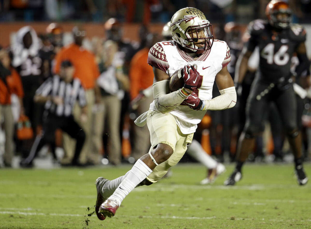 Florida State defensive back Jalen Ramsey runs with the ball after intercepting a pass thrown by Miami quarterback Brad Kaaya in the second half an NCAA college football game, Saturday, Nov. 15, 2014, in Miami Gardens, Fla. Florida State defeated Miami 30-26. (AP Photo/Lynne Sladky)