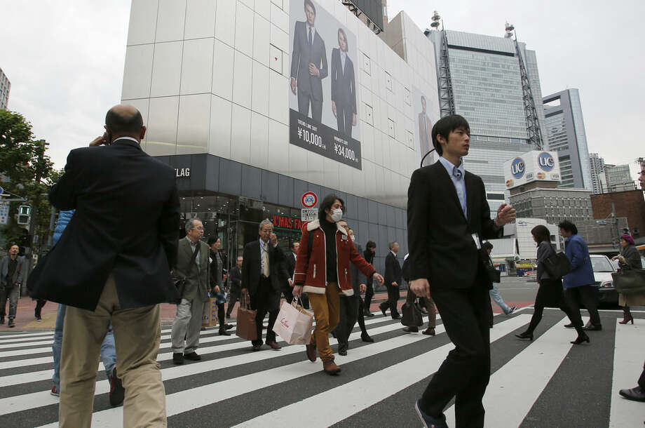 People walk on a pedestrian crossing in Tokyo Monday, Nov. 17, 2014. Japan's economy unexpectedly slid into recession as housing and business investment declined following a sales tax hike, further clouding the outlook for the global economy. (AP Photo/Shizuo Kambayashi)