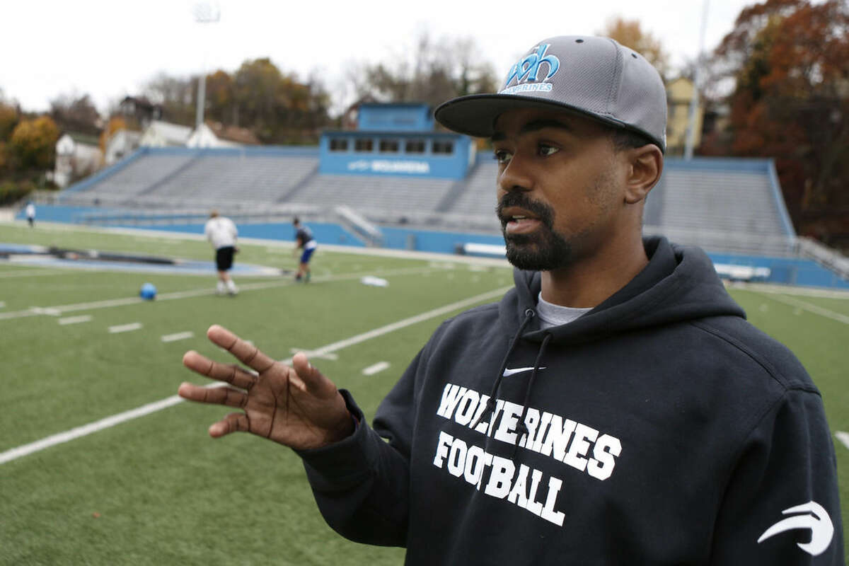 ADVANCE FOR USE MONDAY, NOV. 17, AND THEREAFTER - In this Oct. 30, 2014, photo, Keith Davis, an assistant football coach for Woodland Hills High School, talks about their Coaching Boys into Men program about domestic violence prevention at the team's football field in Turtle Creek, Pa., a suburb east of Pittsburgh. Woodland Hills is among a group of high schools and middle schools across the country participating in Coaching Boys Into Men, a domestic-violence prevention program. Thousands of coaches have received training in how to convey to their players the importance of treating young women with respect and avoiding abusive behavior. (AP Photo/Keith Srakocic)