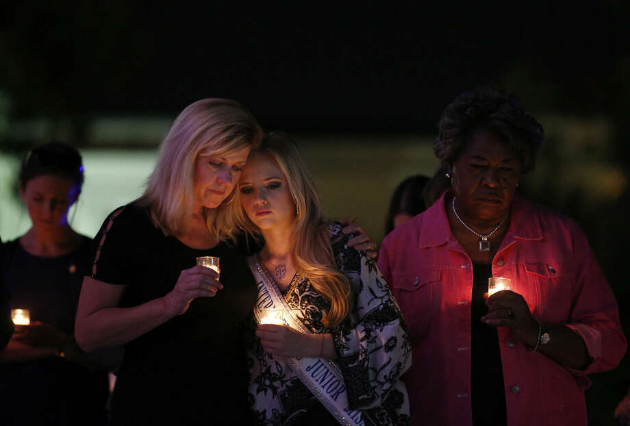 ADVANCE FOR USE MONDAY, NOV. 17, AND THEREAFTER - In this Oct. 1, 2014 photo, Elizabeth Jones, left, and her daughter Taylor Jones, 19, right, attend a candlelight vigil to support Domestic Violence Awareness Month in Montgomery, Ala. Taylor Jones said she was a victim of domestic violence when she was 15-years-old and now stands against domestic violence as an International Junior Miss Teen. Jones says that she started an organization called TIARA Charities (Teens In-action Against Relationship Abuse) in hopes to bring abuse awareness to her community. (AP Photo/Brynn Anderson)