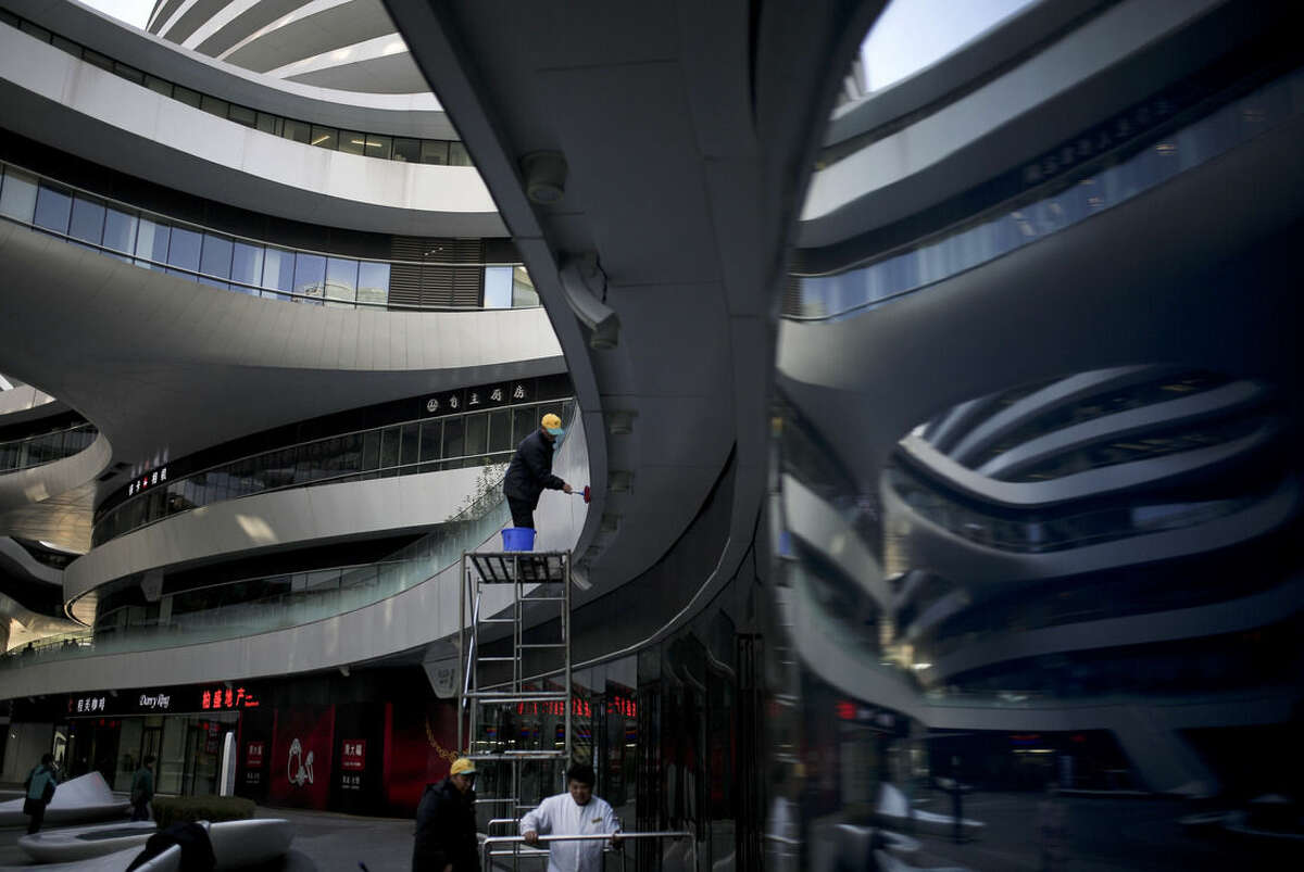 A cleaner stands on a platform wipes on the Galaxy Soho, a newly built commercial building in Beijing, China Monday, Nov. 17, 2014. Under pressure to jolt the lethargic world economy back to life, leaders of G-20 nations on Sunday finalized a plan to boost global GDP by more than $2 trillion over five years. (AP Photo/Andy Wong)