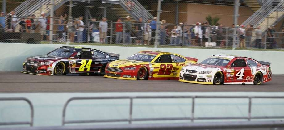 Jeff Gordon (24), Joey Logano (22) and Kevin Harvick race each other during the NASCAR Sprint Cup championship series auto race, Sunday, Nov. 16, 2014 in Homestead, Fla. (AP Photo/Terrry Renna)