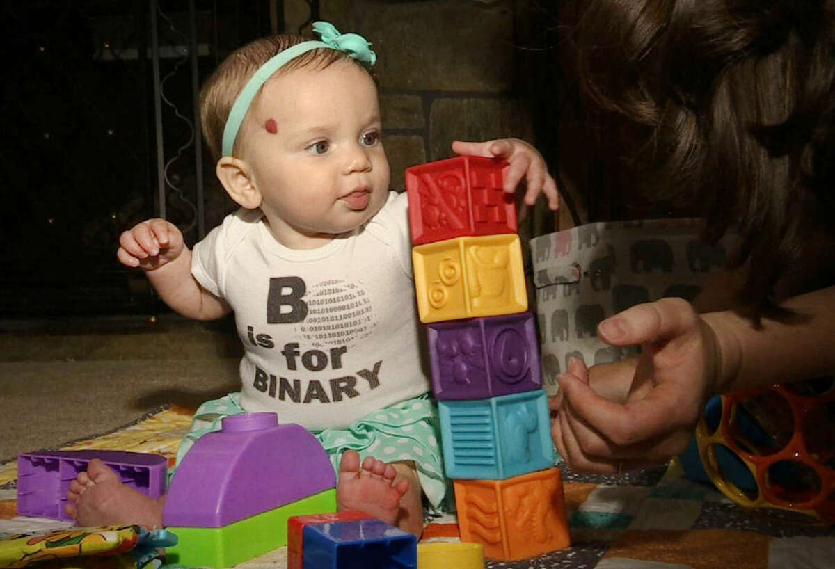 In this July 31, 2014 photo, 6-month-old Marilyn Mathews plays with blocks at home in Langhorne, Penn. She is wearing a shirt that reads,