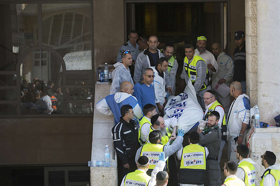 Israeli rescue workers carry a body at the scene of a shooting attack in a Synagogue in Jerusalem, Tuesday, Nov. 18, 2014. Two Palestinians stormed a Jerusalem synagogue on Tuesday, attacking worshippers praying inside with knives, axes and guns, and killing four people before they were killed in a shootout with police, officials said. (AP Photo/Sebastian Scheiner)