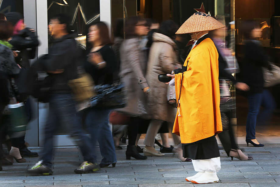 Shoppers walk past a Buddhist monk asking for alms in Tokyo's Ginza shopping district Tuesday, Nov. 18, 2014. The news Monday that the economy contracted 1.6 percent in annual terms in July to September, following a 7.1 percent decline the previous quarter, virtually ensures that Japanese Prime Minister Shinzo Abe will decide Tuesday to delay a tax hike planned for October 2015. (AP Photo/Eugene Hoshiko)