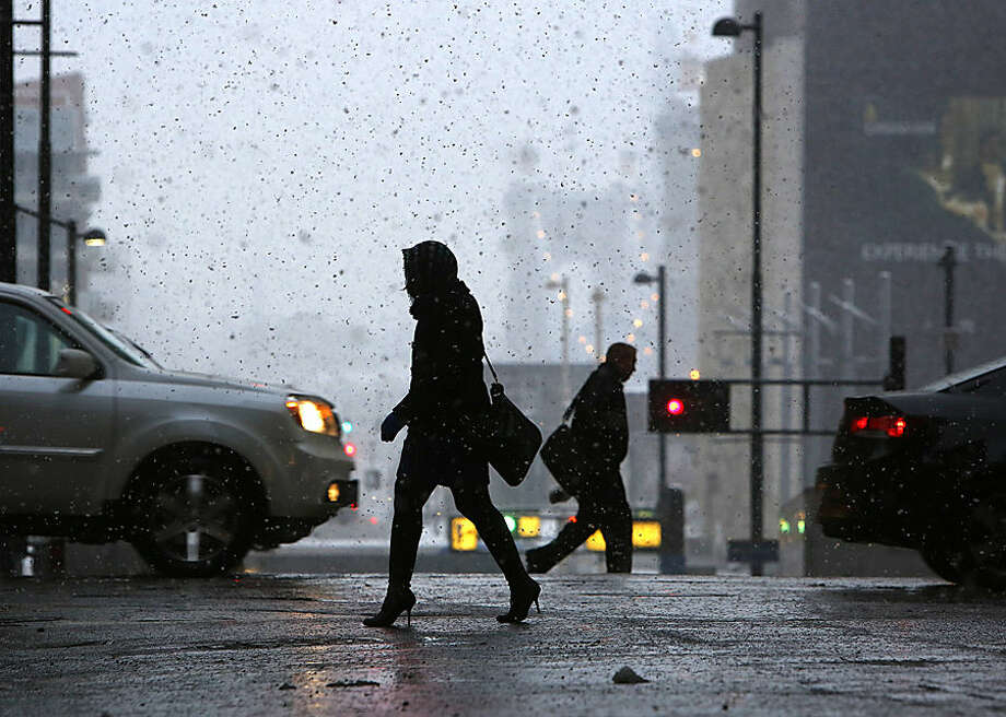 Pedestrians make their way through downtown Cincinnati, Monday morning, Nov. 17, 2014, as the season's first snowfall resulted in thousands of power outages in the Cincinnati area. The National Weather Service reported accumulations of 2 to 4 inches of snow in northern and central Ohio by Monday morning, while the southwest section of the state got 3 to 5 inches. (AP Photo/The Cincinnati Enquirer, Carrie Cochran) MANDATORY CREDIT; NO SALES
