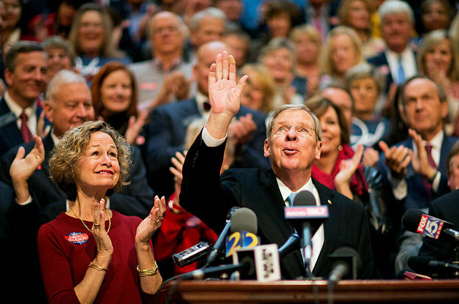 """Sen. Johnny Isakson, R-Ga., right, waves to the crowd while joined by wife Dianne, left, during a news conference to announce his re-election bid for the 2016 campaign at the state Capitol, Monday, Nov. 17, 2014, in Atlanta. The Republican, who'll be seeking his third term, told about 200 supporters Monday that he wants to keep fighting to build up Georgia's infrastructure, pass a balanced budget amendment and reduce federal spending. Gov. Nathan Deal praised Isakson as a """"stable conservative leader."""" (AP Photo/David Goldman)"""