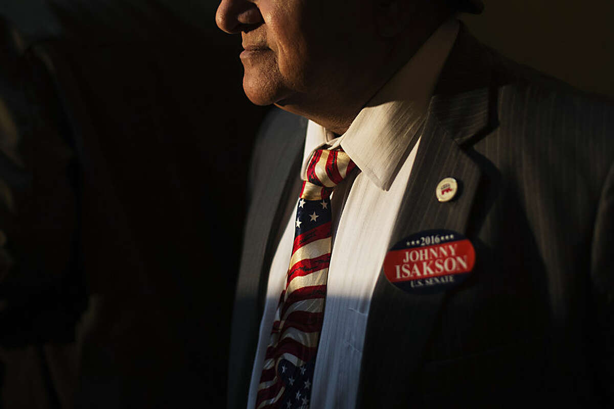 Former Republican Congressional candidate Shahid Malik wears a tie decorated like the American flag and a sticker supporting Sen. Johnny Isakson, R-Ga., at a news conference where Isakson announced his re-election bid for the 2016 campaign at the state Capitol, Monday, Nov. 17, 2014, in Atlanta. The Republican, who'll be seeking his third term, told about 200 supporters Monday that he wants to keep fighting to build up Georgia's infrastructure, pass a balanced budget amendment and reduce federal spending. Gov. Nathan Deal praised Isakson as a