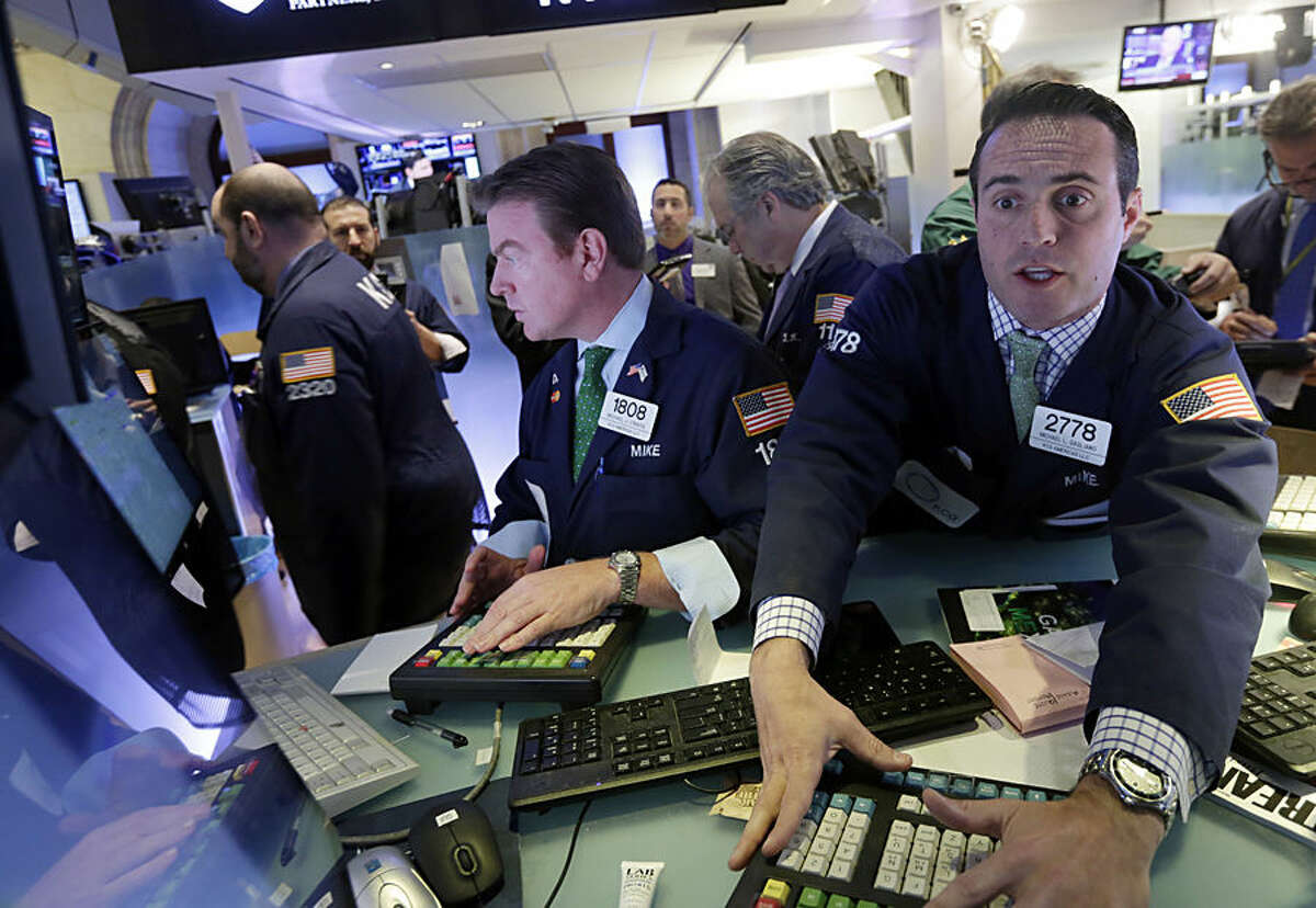 Specialists Michael O'Mara, left, and Michael Gagliano, work at their posts on the floor of the New York Stock Exchange, Monday, Nov. 17, 2014. U.S. stocks are mostly lower in early trading following a sharp drop in Japan overnight. (AP Photo/Richard Drew)
