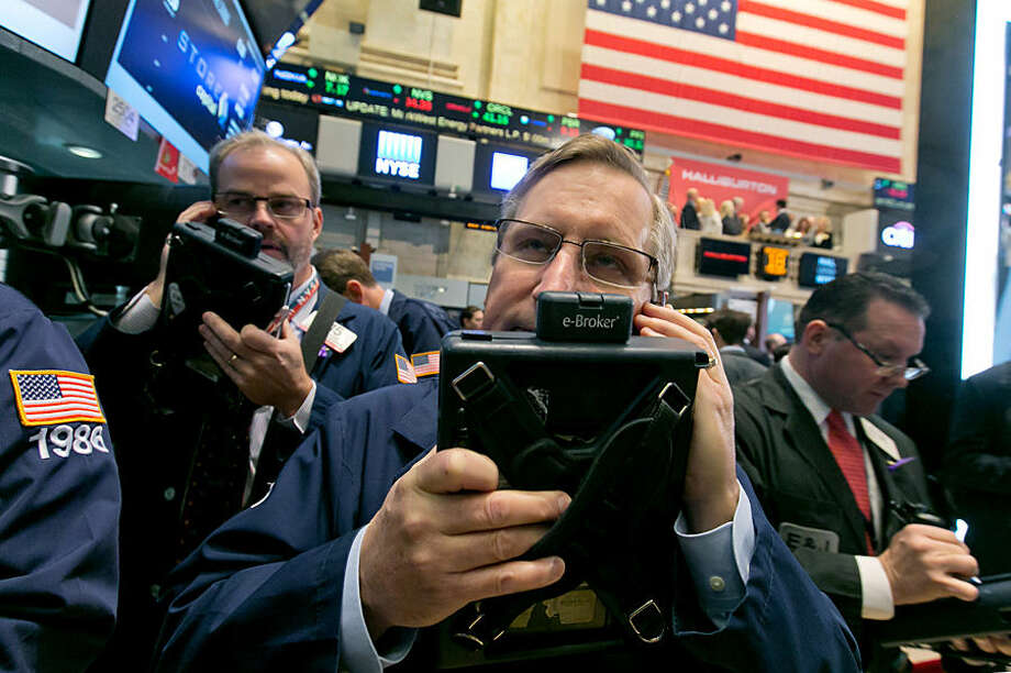 Traders David O'Day, left, and Christopher Fuchs, work on the floor of the New York Stock Exchange, Tuesday, Nov. 18, 2014. Major U.S. stocks opened higher on Tuesday, a day after the Standard & Poor's 500 index set its second record-high close in two days. (AP Photo/Richard Drew)