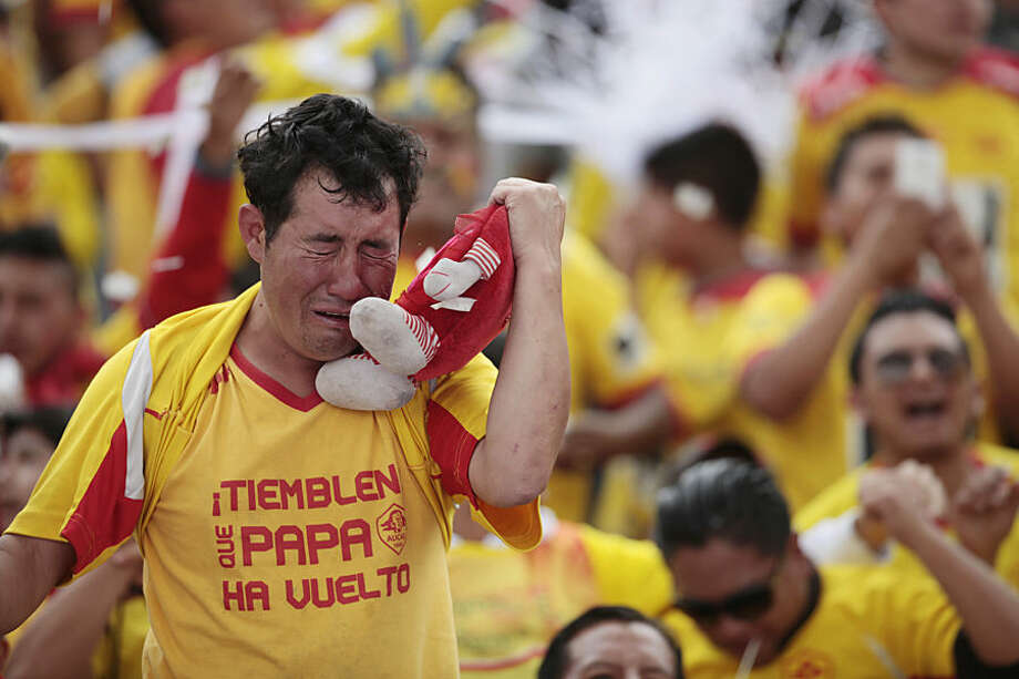 "An Aucas soccer fan, wearing a T-shirt that reads in Spanish ""Shake, daddy's back"" and clutching a heart shaped doll in his team's colors cries after Aucas scored the winning point that moved them back into the top soccer division, Serie A, in Quito, Ecuador, Sunday, Nov. 16, 2014. The Aucas Sociedad Deportiva football club, founded in 1945, hasn't played in Ecuador's top division soccer for the last eight years, and is the only team from the capital that failed to qualify for the Copa Libertadores. Aucas has never won a championship, but the team's fans, spanning all generations, fill stadiums to cheer them on, and say Aucas is not just a team, but a passion. The team's Sunday victory finally put them back in the top division. (AP Photo/Dolores Ochoa)"