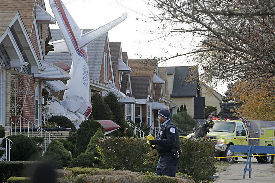 Police and fire officials walk near a small twin-engine cargo plane that crashed into a home on Chicago's southwest side early Tuesday, Nov. 18, 2014. The Aero Commander 500 that had taken off from Midway International Airport slammed into the front of the home and plunged into the basement. Fire Department spokesman Larry Langford says two occupants of the home were unhurt. The pilot was killed in the crash. (AP Photo/M. Spencer Green)