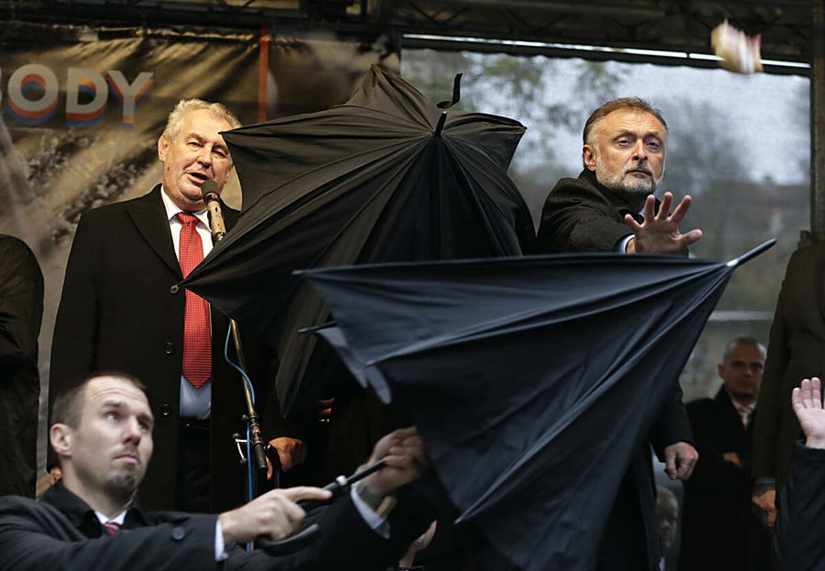 Security personnel use umbrellas to cover Czech Republic's President Milos Zeman, top left, during his speech commemorating the 1989 anti-communist Velvet Revolution in Prague, Czech Republic, Monday, Nov. 17, 2014. During the ceremony protesters booed and pelt objects such as sandwiches, tomatoes and eggs towards the Czech President to protest his demeaning of importance of human rights, a pro-Russian stance in the conflict in Ukraine, using vulgar language and recently downplaying the brutal use of force by police 25 years ago. (AP Photo/Petr David Josek)