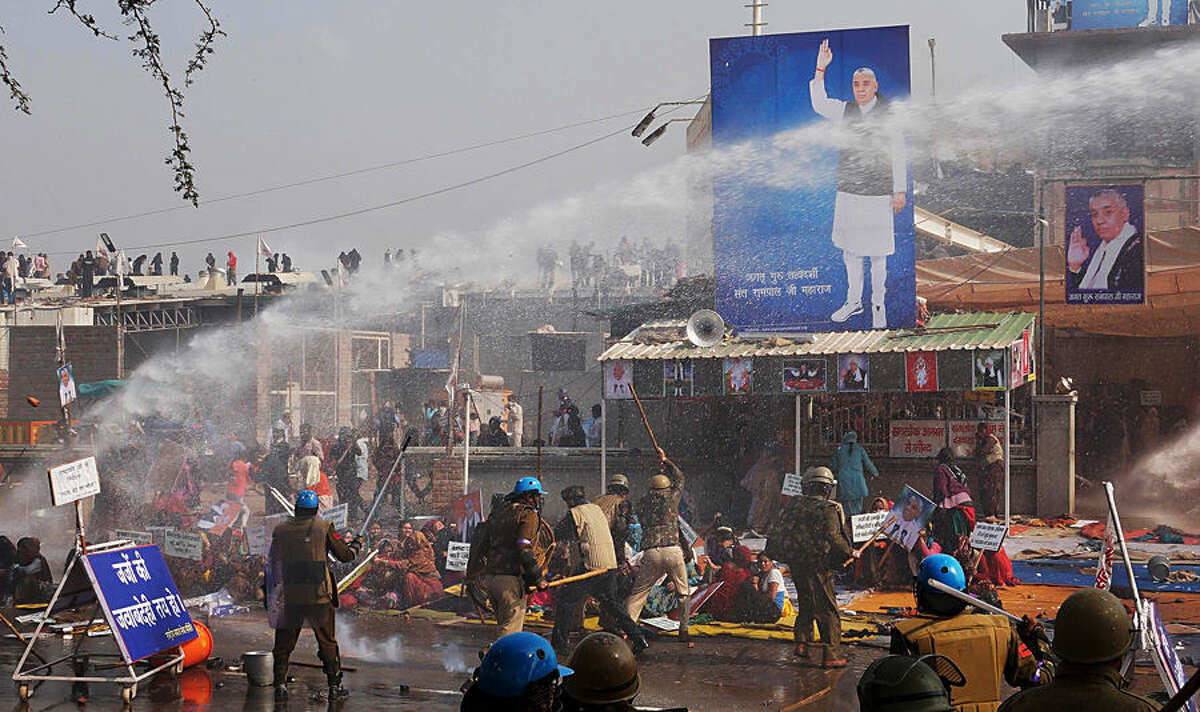 Indian police use batons and water cannon to disperse supporters, as they storm the ashram of controversial Indian guru Sant Rampal, in search of him at Hisar in Haryana state, India, Tuesday, Nov.18, 2014. Several people were injured in the incident. Rampal, had repeatedly ignored court summons to appear for questioning in the 2006 killing of a villager by his supporters. The supporters had formed a human chain around the ashram in an attempt to prevent police from entering. (AP Photo/ Bansilal Basniwal)