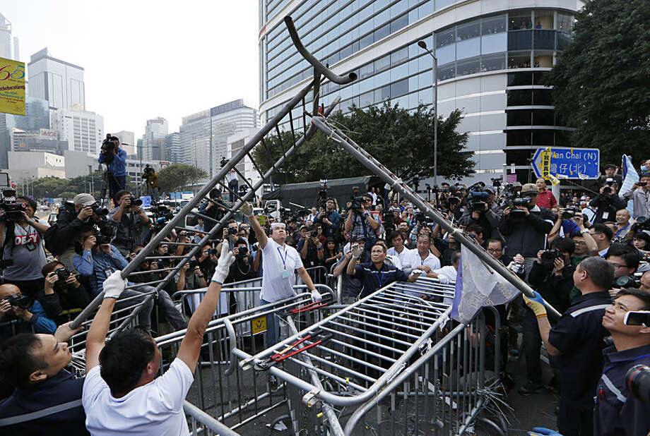 Workers start clearing away barricades at an occupied area outside government headquarters in Hong Kong Tuesday, Nov. 18, 2014. The removal comes after a Hong Kong court granted a restraining order against the protesters last week requiring them to clear the area in front of a tower in the central part of Hong Kong as well a separate order against a second protest site Mong Kok brought by taxi and minibus operators. (AP Photo/Kin Cheung)