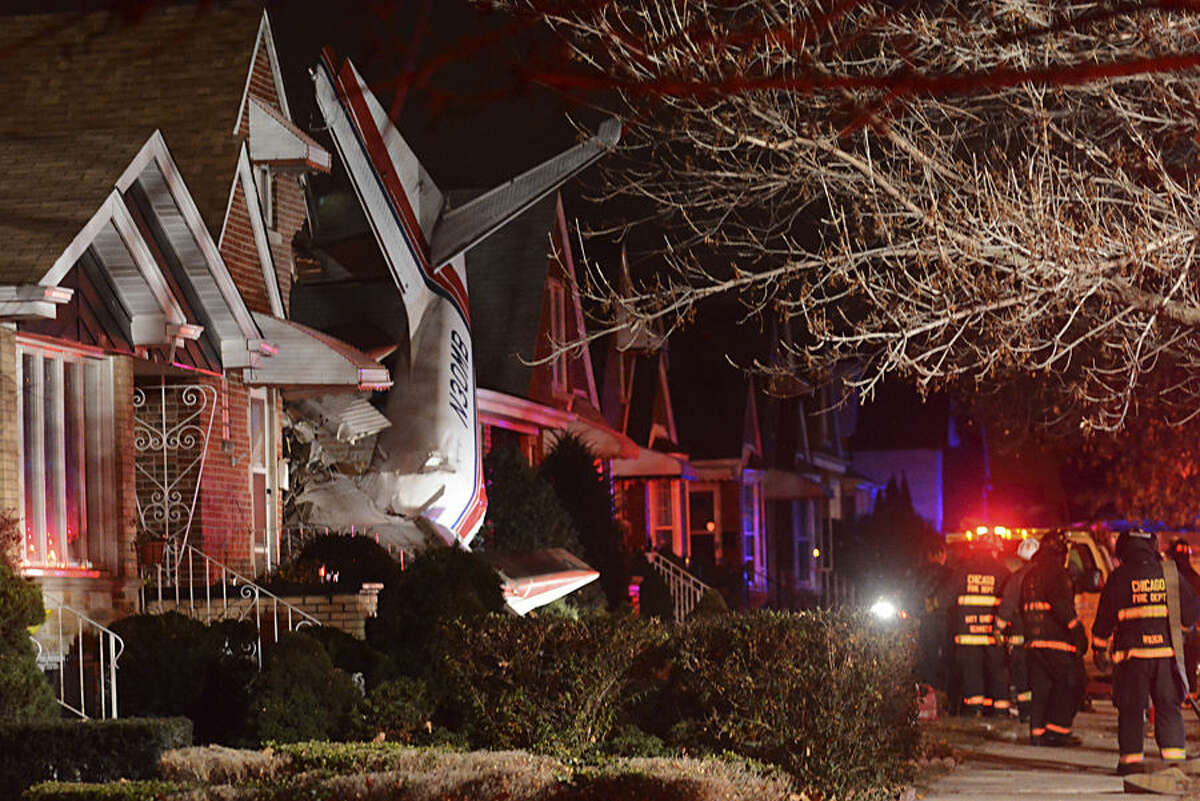 A small twin-engine cargo plane is seen after it crashed into a home on Chicago's southwest side early Tuesday, Nov. 18, 2014, shortly after taking off from Midway International Airport. A fire department spokesman says two occupants of the home were unhurt. Authorities did not immediately release information about the pilot's condition. (AP Photo/Sun-Times Media, Brian Jackson)