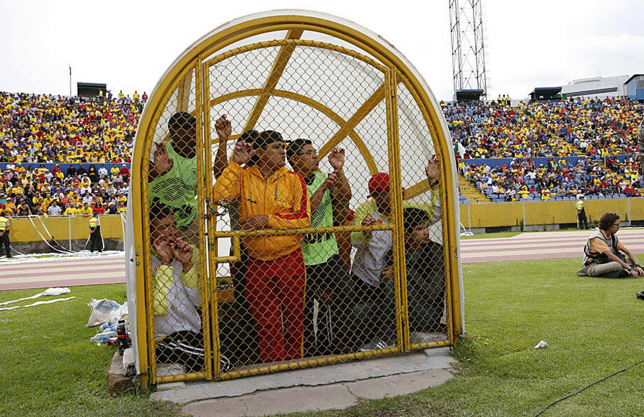 Stadium assistants watch a game between the Aucas and Liga de Portoviejo from inside a gated entry on the sidelines of the field in Quito, Ecuador, Sunday, Nov. 16, 2014. The Aucas Sociedad Deportiva football club, founded in 1945, hasn't played in Ecuador's top division soccer for the last eight years, and is the only team from the capital that failed to qualify for the Copa Libertadores. Aucas has never won a championship, but the team's fans, spanning all generations, fill stadiums to cheer them on, and say Aucas is not just a team, but a passion. The team's Sunday victory finally put them back in the top division. (AP Photo/Dolores Ochoa)