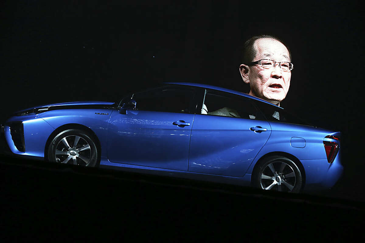The image of Toyota Motor Corp. Product Planning Group Deputy Chief engineer Yoshikazu Tanaka is projected as he delivers a speech during a press unveiling of the all new fuel cell vehicle FCV