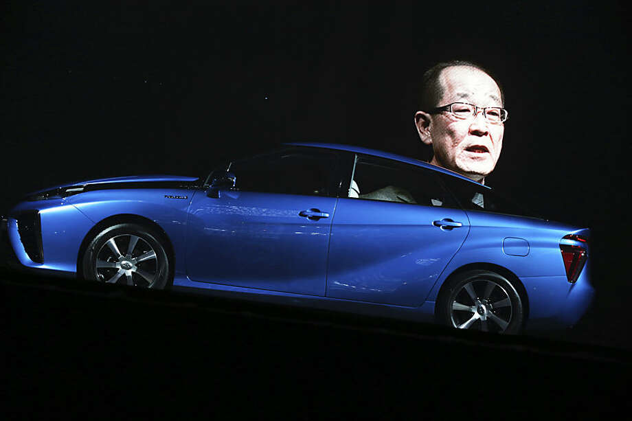 "The image of Toyota Motor Corp. Product Planning Group Deputy Chief engineer Yoshikazu Tanaka is projected as he delivers a speech during a press unveiling of the all new fuel cell vehicle FCV ""Mirai"" in Tokyo, Tuesday, Nov. 18, 2014. The world's largest automaker announced Tuesday that it will begin selling fuel cell cars in Japan on Dec. 15 and in the U.S. and Europe in mid-2015. The sporty-looking, four-door Toyota Mirai will retail for 6.7 million yen ($57,600) before taxes. Toyota Motor Corp hopes to sell 400 in Japan and 300 in the rest of the world in the first year. (AP Photo/Eugene Hoshiko)"