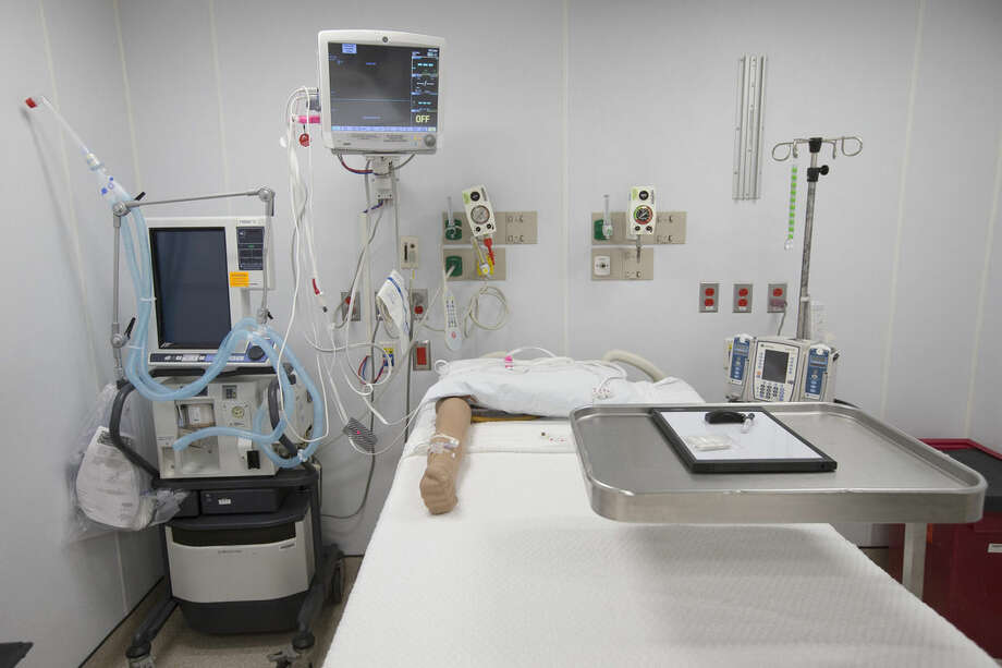 In this Friday, Nov. 14, 2014 photo, a prosthetic arm for IV training rests on a bed in a patient care room inside a new custom-built bio-containment unit for potential Ebola cases at Mount Sinai Hospital in New York. The unit, built over two weeks, is completely separate from the main medical buildings and can house three patients simultaneously. (AP Photo/John Minchillo)
