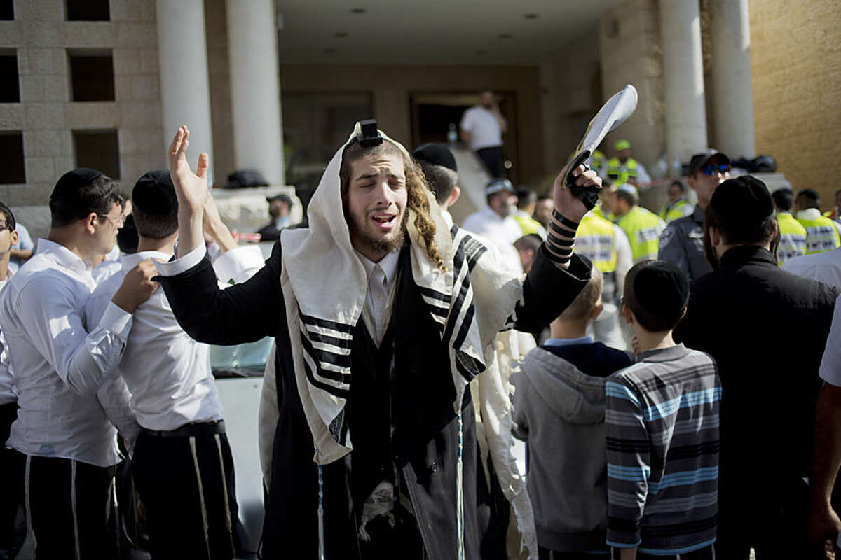 An ultra-Orthodox Jewish man prayers as Israeli rescue workers clean the scene of a shooting attack in a Synagogue in Jerusalem, Tuesday, Nov. 18, 2014. Two Palestinians stormed a Jerusalem synagogue on Tuesday, attacking worshippers praying inside with knives, axes and guns, and killing four people before they were killed in a shootout with police, officials said. (AP Photo/Ariel Schalit)