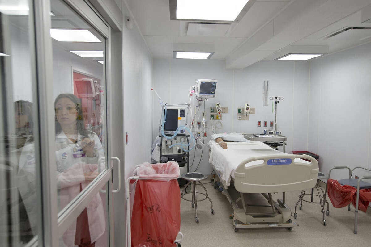 In this Friday, Nov. 14, 2014 photo, a medical worker stands outside a patient care room in a new custom-built bio-containment unit for potential Ebola cases at Mount Sinai Hospital, in New York. The unit, built over two weeks, is completely separate from the main medical buildings and can house three patients simultaneously. (AP Photo/John Minchillo)