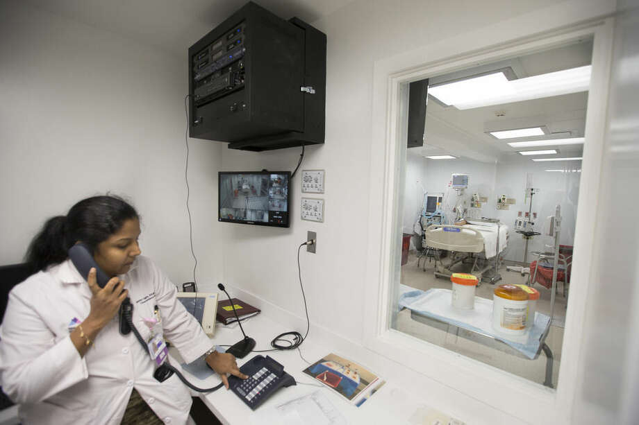 In this Friday, Nov. 14, 2014 photo, a nurse sits beside a closed-circuit monitoring system outside a patient care room in a new custom-built bio-containment unit for potential Ebola cases at Mount Sinai Hospital, in New York. The unit, built over two weeks, is completely separate from the main medical buildings and can house three patients simultaneously. (AP Photo/John Minchillo)