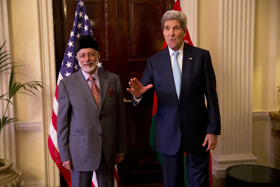 U.S. Secretary of State John Kerry, right, waves as he stands with Oman Foreign Minister Yusuf Bin Alawi bin Abdullah after arriving for their meeting at the official residence of the U.S. ambassador to Britain, Winfield House, in London, Tuesday, Nov. 18, 2014. (AP Photo/Matt Dunham)