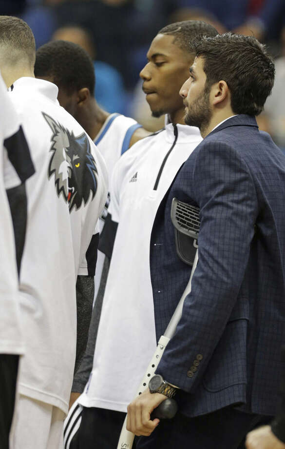 Minnesota Timberwolves' Ricky Rubio, right, of Spain, joins teammates while on crutches prior to an NBA basketball game against the New York Knicks, Wednesday, Nov. 19, 2014, in Minneapolis. Rubio is recovering form a high ankle sprain. (AP Photo/Jim Mone)