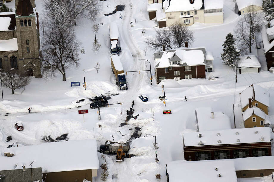 Cars make their way through South Buffalo, N.Y.,Wednesday, Nov. 19, 2014. The Buffalo area found itself buried under as much as 5½ feet of snow Wednesday, with another lake-effect storm expected to bring 2 to 3 more feet by late Thursday. (AP Photo/The Buffalo News, Derek Gee) TV OUT; MAGS OUT; MANDATORY CREDIT; BATAVIA DAILY NEWS OUT; DUNKIRK OBSERVER OUT; JAMESTOWN POST-JOURNAL OUT; LOCKPORT UNION-SUN JOURNAL OUT; NIAGARA GAZETTE OUT; OLEAN TIMES-HERALD OUT; SALAMANCA PRESS OUT; TONAWANDA NEWS OUT