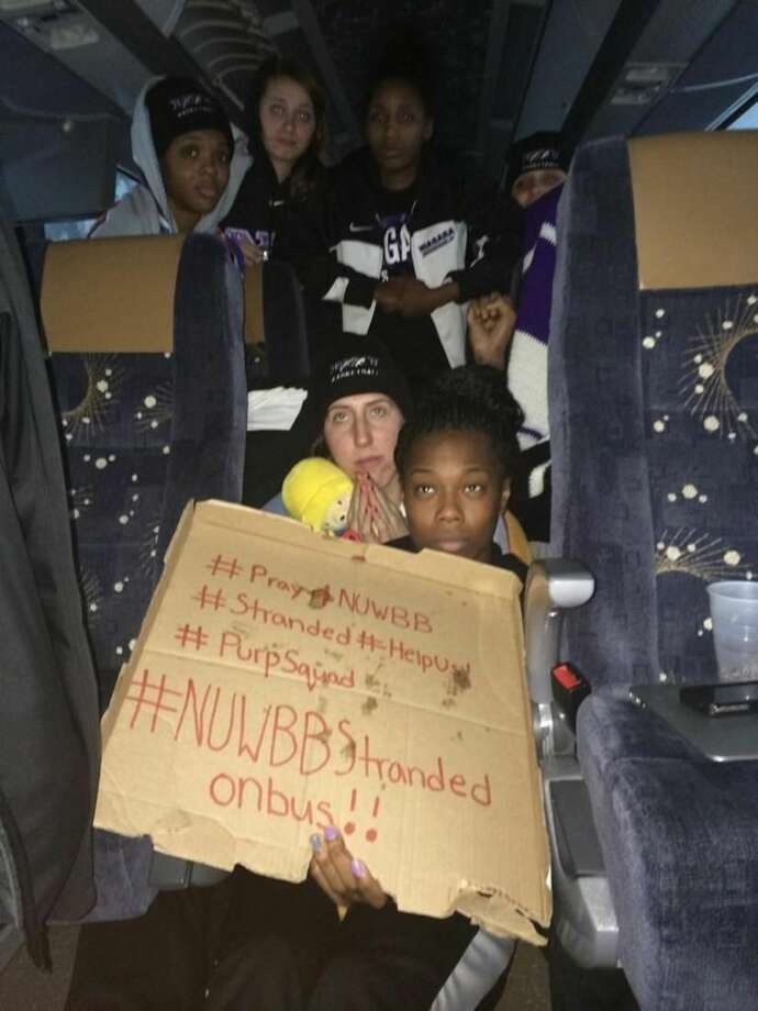 This photo provided by Chelsea Andorka, the Niagara University women's basketball team spokeswoman, shows the team holding a sign while their bus was snowbound on the New York State Thruway in the middle of a lake-effect storm that has dropped more than 4 feet of snow near Lackawanna, N.Y., Tuesday, Nov. 18, 2014. Andorka says the team's bus was headed back from a loss in Pittsburgh when it came to a halt at 2 a.m. Tuesday about two miles from the Lackawanna exit near Buffalo. About 25 people are on the bus, including 15 players plus staff, the coach and coach's family. (AP Photo/Chelsea Andorka)