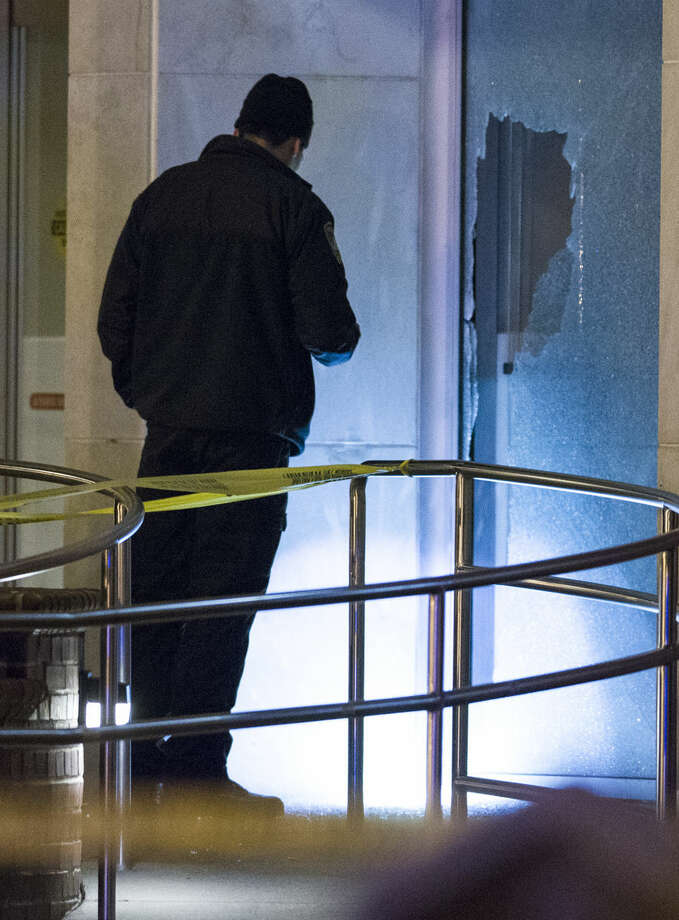 A Tallahassee police officer investigates a broken window near a body after a shooting outside the Strozier library on the Florida State University campus in Tallahassee, Fla. Nov 20, 2014. The gunman was shot and killed by police officers according to Tallahassee Police spokesman Dave Northway. (AP Photo/Mark Wallheiser)