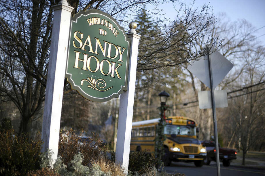 "FILE - In this Dec. 4, 2013 file photo, a school bus drives past a sign reading Welcome to Sandy Hook, in Newtown, Conn., where 26 people were killed by a gunman inside Sandy Hook Elementary School. A new play about the massacre at the Sandy Hook Elementary School will have a benefit reading in December in New York City to commemorate the second anniversary of the tragedy. Eric Ulloa's ""26 Pebbles,"" which was adapted from transcripts of interviews with people touched by the shootings, will have a staged reading Dec. 15 at the Culture Project's The Lynn Redgrave Theater. The director will be Igor Goldin and prices range from $50-$150. (AP Photo/Jessica Hill, File)"