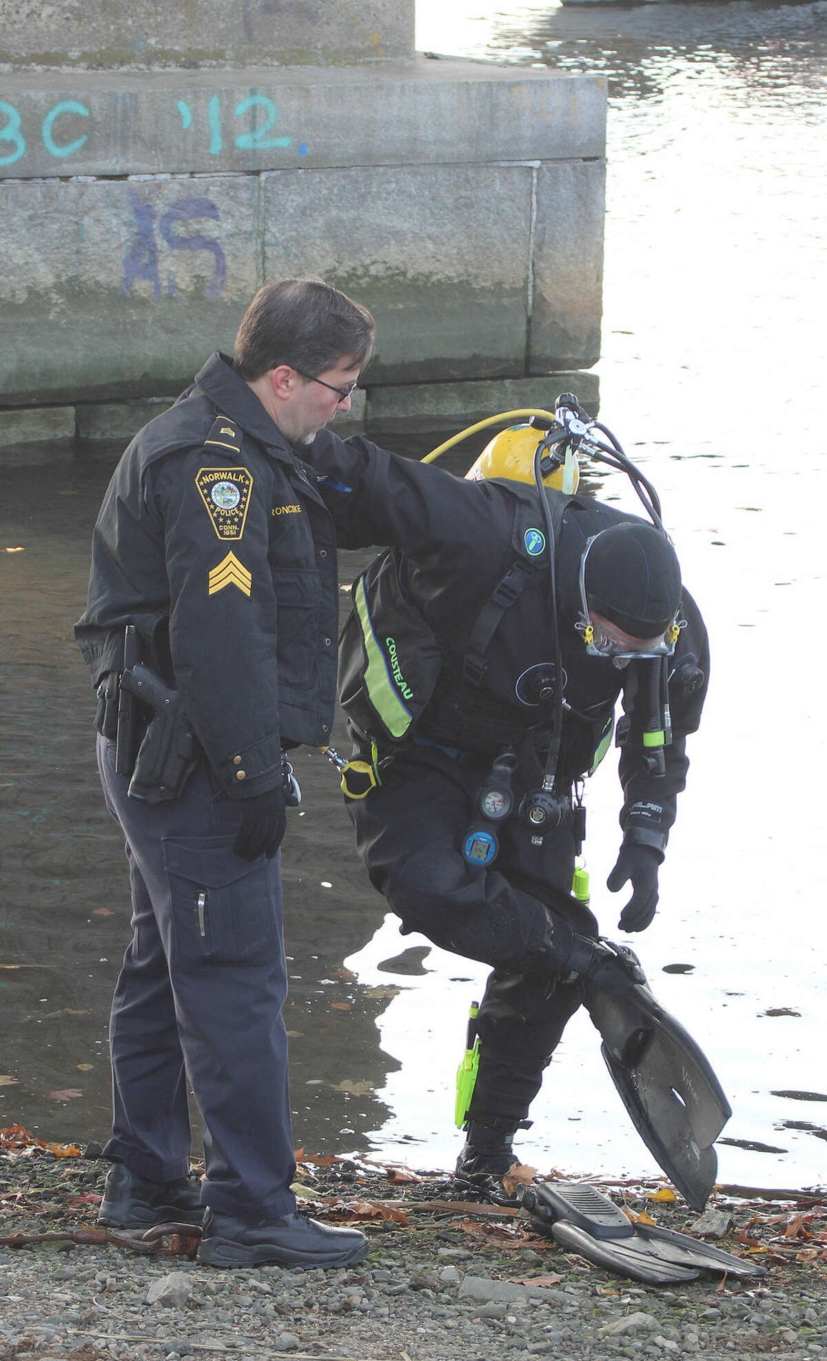 Hour photo/Chris Bosak Thomas Roncinske helps Norwalk Police officer Bruce Lovallo during a diving training session held Thurday in the Norwalk River.