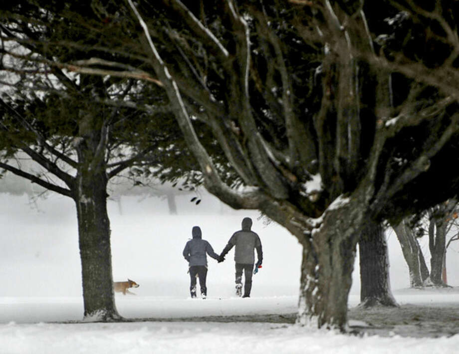 A couple take their dog for a walk on the trails through the Watertown Golf Club in Watertown, N.Y. on Thursday, Nov. 20, 2014. A new blast of lake-effect snow pounded Buffalo for a third day piling more misery on a city already buried by an epic, deadly snowfall that could leave some areas with nearly 8 feet of snow on the ground when it's all done. (AP Photo/The Watertown Daily Times, Amanda Morrison)