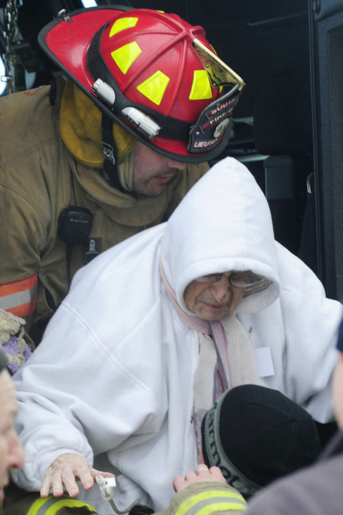 A firefighter from South Line lowers an elderly patient as she arrives to the Appletree Mall in Cheektowaga, N.Y., Thursday, Nov. 20, 2014. About 180 patients from the facility were moved after officials questioned sustainability of the the roof from the snowfall. Roofs began to creak and collapse under the weight of excessive snow as another storm added to epic snowfall in western New York state. (AP Photo/Gary Wiepert)