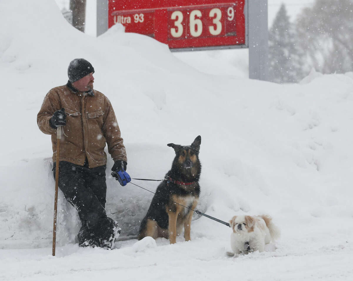 Tom Kitson of Ayr, Ont., with companions Dug and Champ, waits for a friend outside a convenient store on Thursday, Nov. 20, 2014, in West Seneca, N.Y. A new blast of lake-effect snow pounded Buffalo for a third day piling more misery on a city already buried by an epic, deadly snowfall that could leave some areas with nearly 8 feet of snow on the ground when it's all done. (AP Photo/Mike Groll)