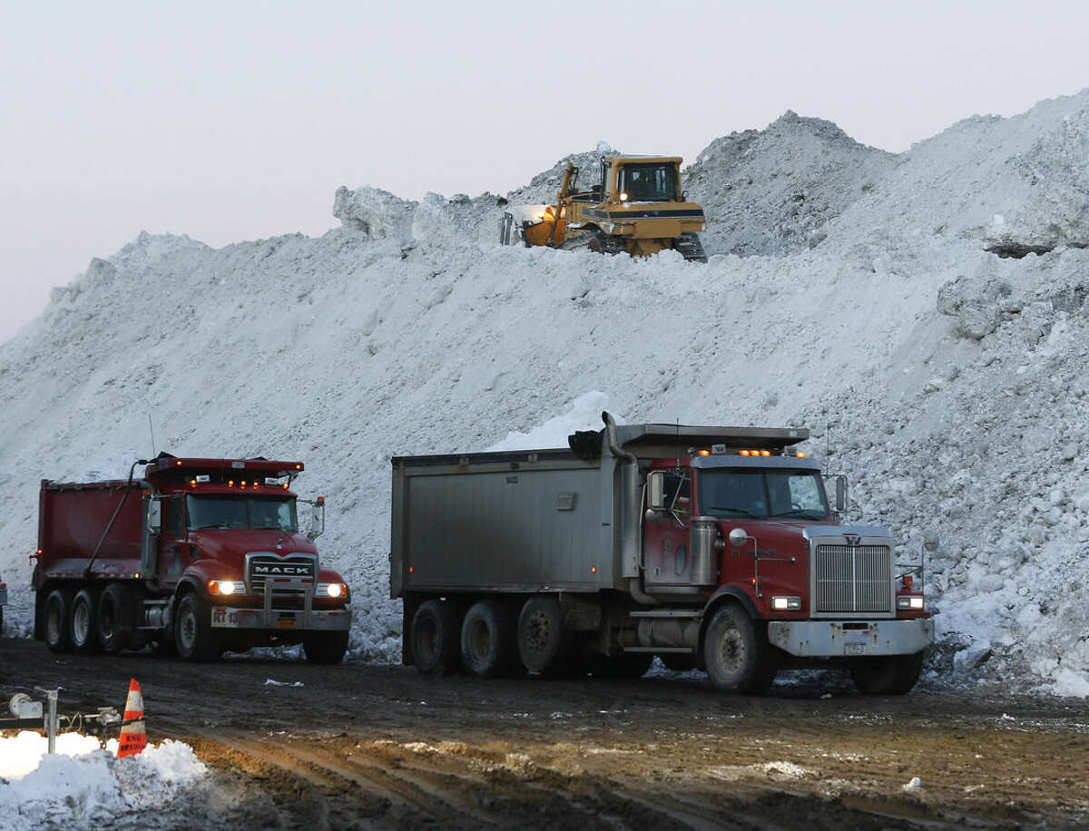 Dump trucks wait to unload snow at the Central Terminal that was removed from south Buffalo neighborhoods after heavy lake-effect snowstorms on Friday, Nov. 21, 2014, in Buffalo, N.Y. A snowfall that brought huge drifts and closed roads in the Buffalo area finally ended Friday, yet residents still couldn't breathe easy, as the looming threat of rain and higher temperatures through the weekend and beyond raised the possibility of floods and more roofs collapsing under the heavy loads. (AP Photo/Mike Groll)