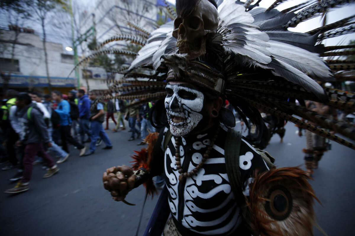 A protester dressed in an Aztec costume walks during a massive march in Mexico City, Thursday, Nov. 20, 2014. Protesters marched to demand authorities find 43 missing college students, trying to step up pressure on the government on a day traditionally reserved for the celebration of the 1910-17 Revolution. (AP Photo/Eduardo Verdugo)