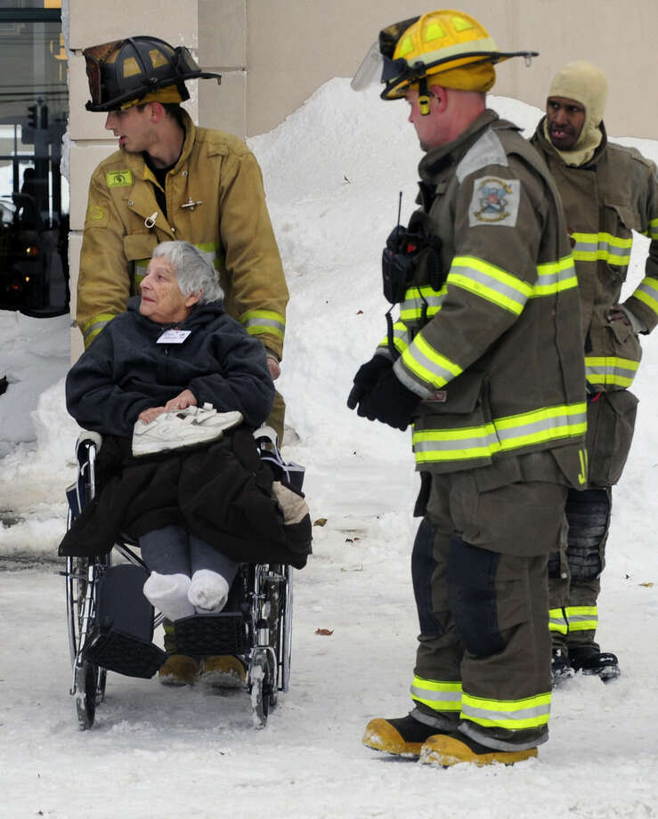 Firefighters from Cheektowaga and Depew assist a patient from from Garden Gate Health Care Facility to the Appletree Mall in Cheektowaga, N.Y., Thursday, Nov. 20, 2014. About 180 patients from the facility were moved after officials questioned sustainability of the the roof from the snowfall. Roofs began to creak and collapse under the weight of excessive snow as another storm Thursday added to epic snowfall in western New York state. (AP Photo/Gary Wiepert)